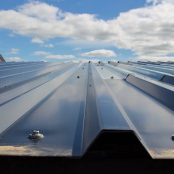 Metal roofing contractors installing a metal roof on a commercial building